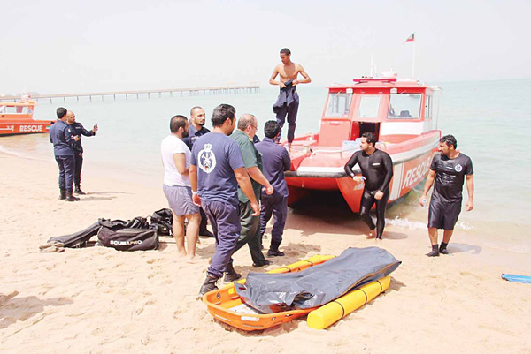 Firemen after recovering the body of young Kuwaiti citizen who died while swimming
