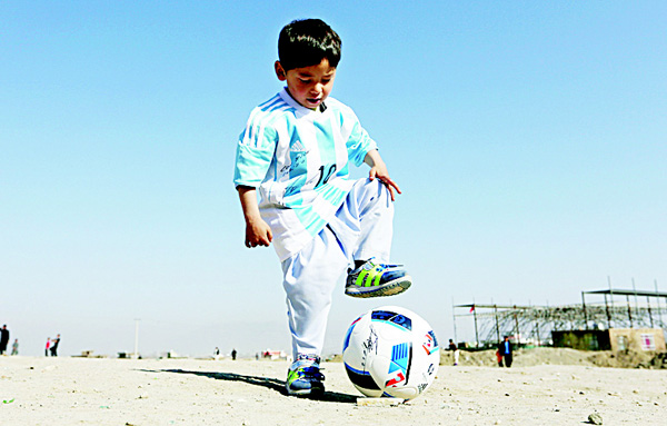 In this Friday, Feb 26, 2016 file photo, Murtaza Ahmadi, a five-year-old Afghan Lionel Messi fan plays with a soccer ball during a photo opportunity as he wears a shirt signed by Messi, in Kabul, Afghanistan. The father of Ahmadi says the family was forced to leave Afghanistan amid constant telephone threats. (AP)