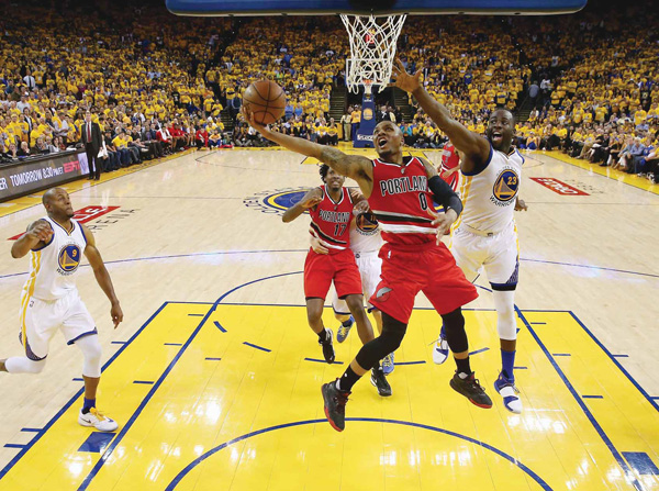 Damian Lillard #0 of the Portland Trail Blazers goes up for a shot against Draymond Green #23 of the Golden State Warriors during Game Five of the Western Conference Semifinals during the 2016 NBA Playoffs on May 11, 2016 at Oracle Arena in Oakland, California. (AFP)