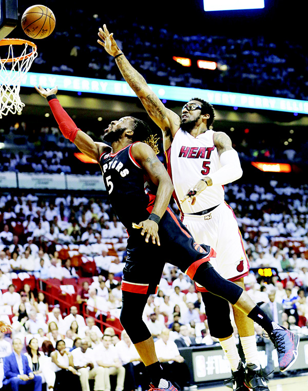 Toronto Raptors forward DeMarre Carroll (5) lays up the ball for a basket as Miami Heat forward Amar'e Stoudemire (5) defends, during the first half of Game 4 of an NBA second-round basketball Playoff Series on May 9, in Miami. (AP)