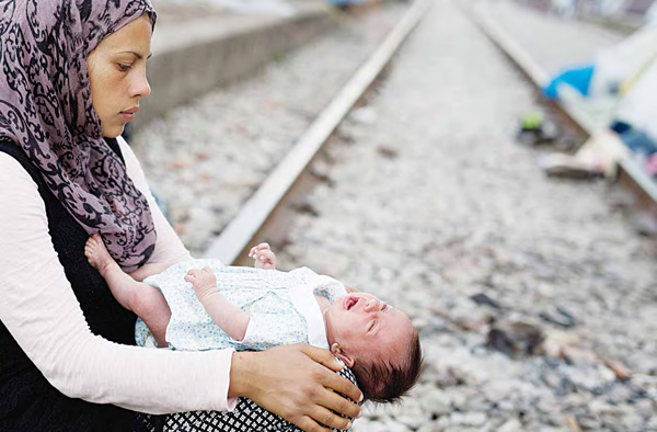19-year-old Rajad, a Syrian woman, holds her 42-day-old baby girl Yasmin, at a makeshift refugee camp of the northern Greek border point of Idomeni, Greece, on May 13. More than 9,000 refugees and migrants are camped in Idomeni as about 54,000 people are currently stranded in Greece, after the European Union and Turkey reached a deal designed to  stem the flow of refugees into Europe's prosperous heartland. (AP)