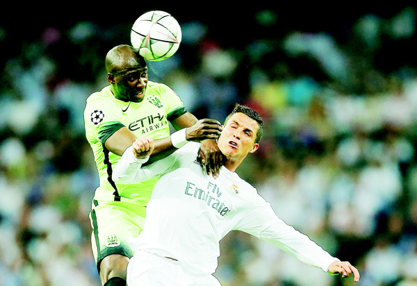 Manchester City's Eliaquim Mangala (top), wins a header over Real Madrid's Cristiano Ronaldo during the Champions League semifinal second leg soccer match between Real Madrid and Manchester City at the Santiago Bernabeu Stadium in Madrid, on May 4. (AP)