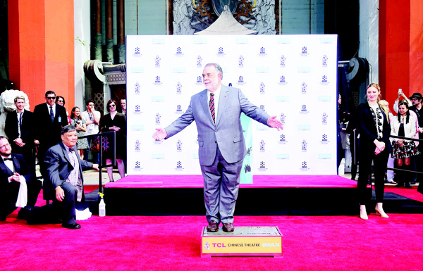 Director Francis Ford Coppola gestures while standing on the cement at his Hand and Footprint Ceremony in front of the TCL theater in Hollywood, California on April 29. The US film director was honored as part of the 2016 TCM Classic Film Festival. (AFP)
