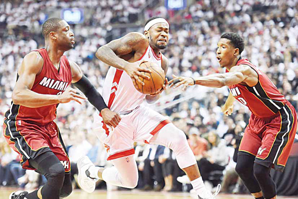 Toronto Raptors' Terrence Ross (center), drives to the net between Miami Heat's Dwyane Wade (left), and Josh Richardson during the first half of Game 7 of the NBA Basketball Eastern Conference semifinals in Toronto, May 15. (AP)