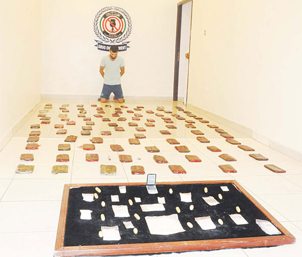 The accused with the hashish and other drugs found in his possession.- MoI photo