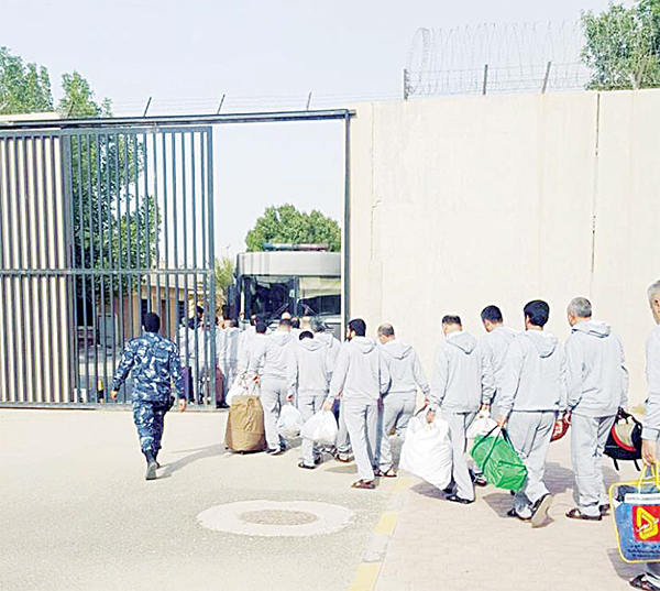 Iranian inmates are seen exiting the gate as they are being handed over to Tehran.