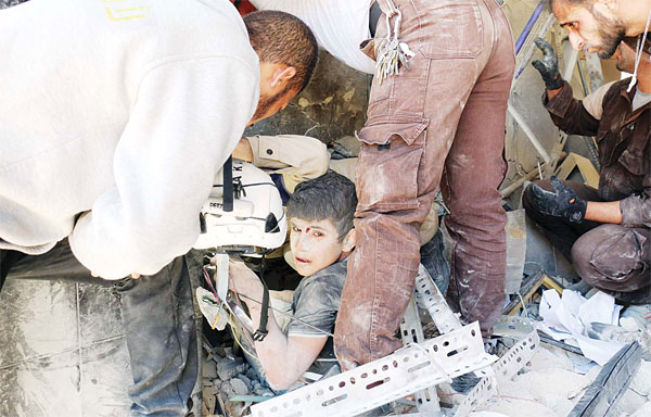 Syrian civil defence volunteers help a boy out of the rubble following a reported attack by Syrian government forces on May 30 , in the Tariq al-Bab neighbourhood in the northern city of Aleppo. (AFP)
