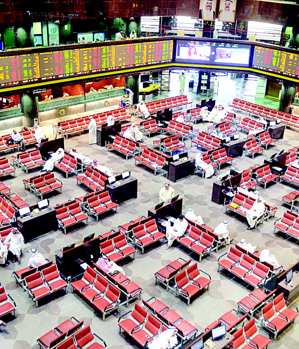 Traders watch stocks movements at the floor of the Kuwait Stock Exchange. The bourse sank 28.45 pts on Wednesday.