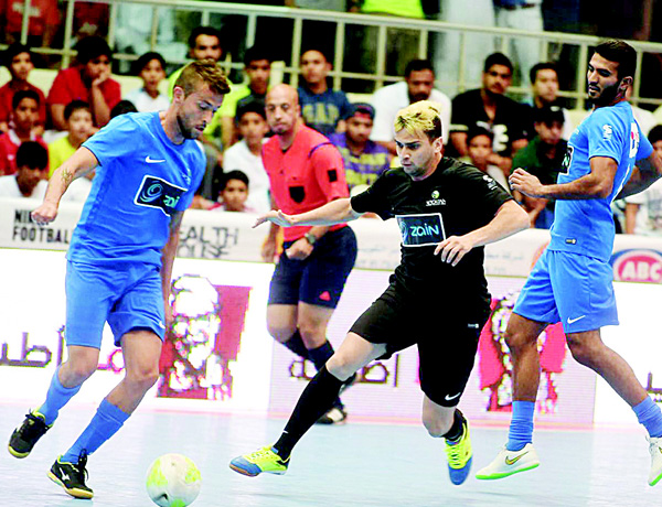 Players vie for possession of the ball in one of the matches during the Ramadan Indoor Tournament.
