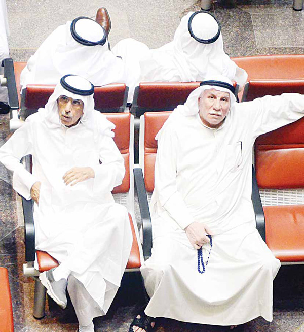 Traders watch share movements on the floor of the Kuwait Stock Exchange. The bourse edged down 1.18 pts on Thursday.