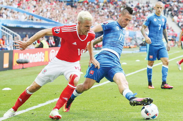 Wales' Aaron Ramsey (left), and Slovakia's Marek Hamsik vie for the ball during the Euro 2016 Group B soccer match between Wales and Slovakia, at the Nouveau Stadium in Bordeaux, France on June 11. (AP)