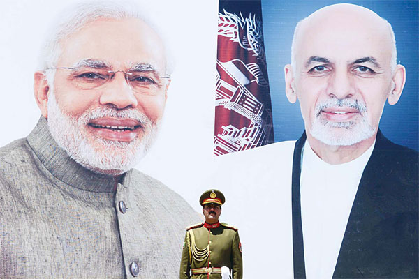 An Afghan guard of honour stands under a poster bearing the images of Indian Prime Minister Narendra Modi (left), and Afghan president Ashraf Ghani ahead of the inauguration of the Salma Hydroelectric Dam in Herat on June 4, 2016. (AFP)