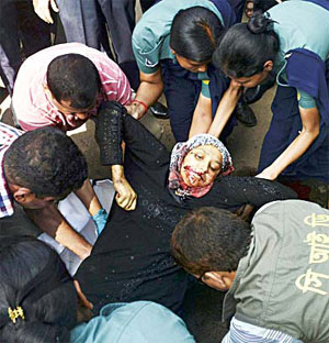 The dead body of Mahmuda Aktar, the wife of a top Bangladeshi antiterror officer, is lifted up by police after she was shot dead near her home in Chittagong on June 5. (AFP)