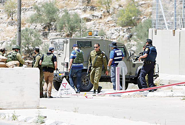 Israeli security forces inspect the scene of a stabbing attack at a checkpoint near the West Bank city of Tulkaram on June 2. A female Palestinian tried to stab an Israeli soldier near of Tulkarem and was shot dead, the army said, the latest in a series of such incidents since October. (AFP)