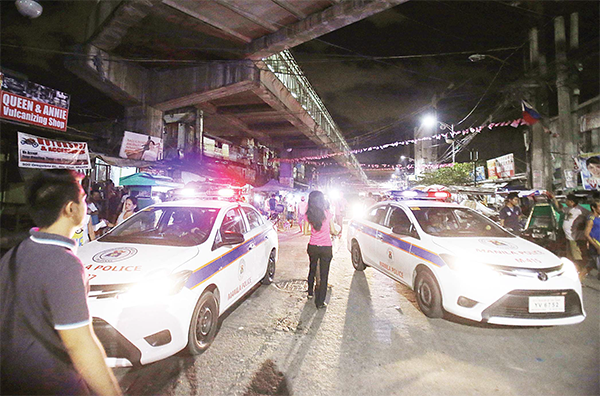 In this June 8, 2016 file photo, police cars block a street as they enforce an overnight curfew for minors in Manila, Philippines. Even before he takes his oath of office on Thursday, Philippine president-elect Rodrigo Duterte's vow to kill drug criminals appear already being rolled out. At least dozens of suspected drug criminals have either been killed in shootouts with police or mysteriously found dead on the streets in what some fear is a portent of things to come. (AP)