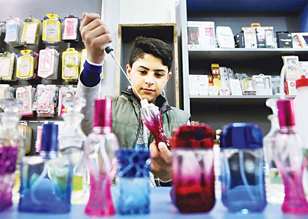 In this April 1, 2016 photo, thirteen-year-old Syrian refugee Ali Rajab, fills bottles of perfume at a shop in Beirut, Lebanon. Rajab is on his feet an average of 12 hours a day, cleaning, filling perfume bottles and helping sell mobile phones at the shop in Beirut where he works. (AP)