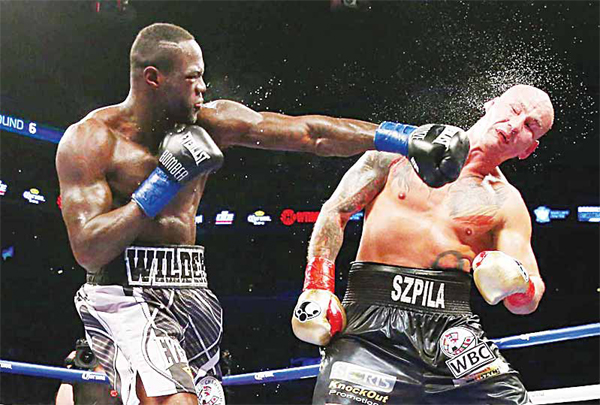 In this file photo, Deontay Wilder punches Artur Szpilka during their WBC Heavyweight Championship bout in January 2016. (AFP)