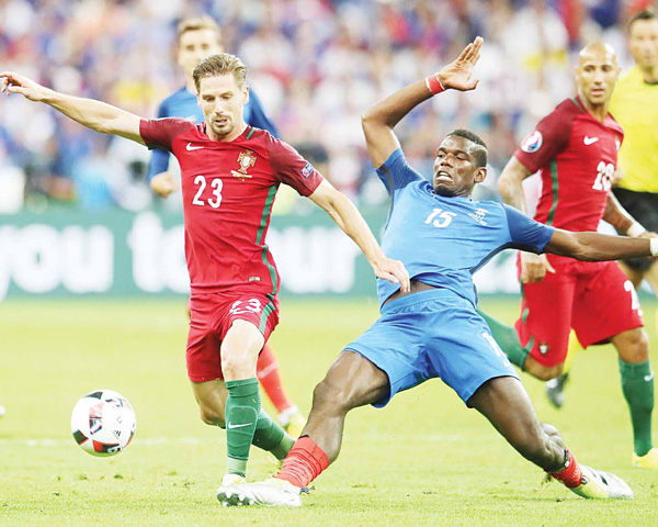 Portugal's Adrien Silva (left), France's Paul Pogba battle for ball duirng the Euro 2016 final soccer match between Portugal and France at the Stade de France in Saint-Denis, north of Paris, on July 10. (AP)