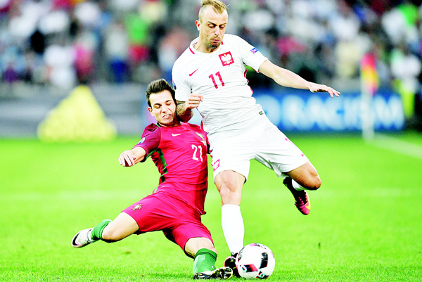 Portugal's Cedric (left), and Poland's Kamil Grosicki challenge for the ball during the EURO 2016 quarter-final soccer match between Poland and Portugal, at the Velodrome Stadium in Marseille, France, June 30. (AP)