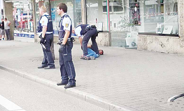 In this grab taken from video, police officers arrest a man close to a machete (front right), after an attack in Reutlingen, Germany on July 24. A Syrian man killed a woman with a machete and wounded two others Sunday outside a bus station in the southwestern German city of Reutlingen before being arrested. Police said there were no indications pointing to terrorism. (AP)