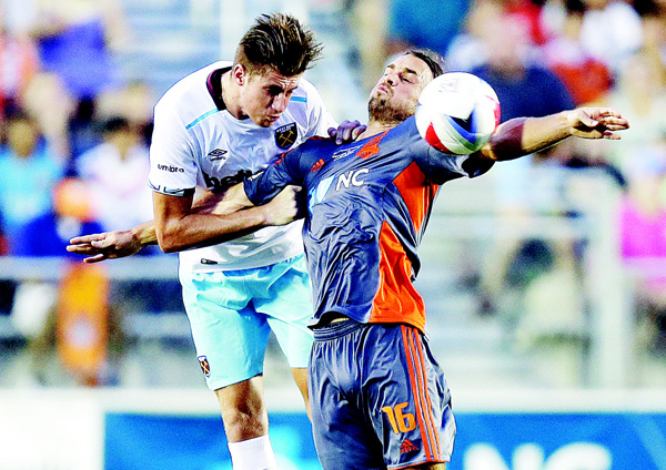 West Ham United's Reece Burke (left), and Carolina Railhawks' Matt Fondy (16) jump for the ball in the first half of an international friendly soccer match in Cary, NC, on July 12. (AP)