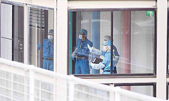 Police investigators work at the Tsukui Yamayuri-en, a facility for the disabled where a number of people were killed and dozens injured in a knife attack in Sagamihara. (AP)