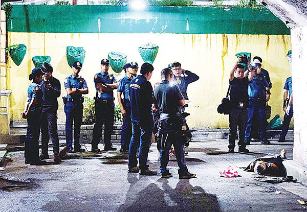 In this picture taken on July 8 police offi cers investigate the dead body of an alleged drug dealer (right), his face covered with packing tape and a placard reading 'I'm a pusher', on a street in Manila. Philippine President Rodrigo Duterte on July 1 urged communist rebels to start killing drug traffi ckers, adding another layer to a controversial war on crime in which he has warned thousands will die. (AFP)