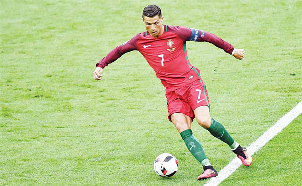 Portugal's forward Cristiano Ronaldo runs with the ball during the EURO 2016 final football match between Portugal and France at the Stade de France in Saint-Denis, north of Paris on July 10. (AFP)