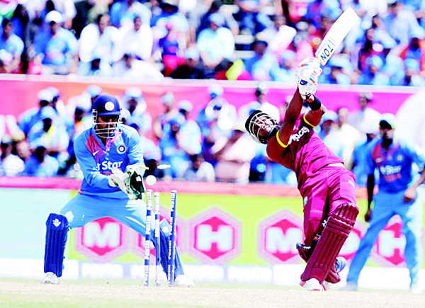 West Indies' Dwayne Bravo (right), is bowled by India's Amit Mishra as India's MS Dhoni (left), looks on during the second Twenty20 international cricket match on Aug 28, in Lauderhill, Fla. (AP)