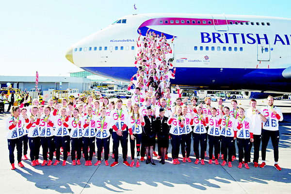 Members of the British Olympic Team pose for a photograph with their medals after they arrive back from the Rio 2016 Olympic Games in Brazil on a gold-tipped Boeing 747, at Heathrow airport in London on Aug 23. Twenty years after a stinging Olympic failure, Britain has risen from the ashes to become a sporting 'superpower'. Rival nations have been left confounded by Team GB's cool performance with 27 golds out of 67 won in Rio which gave them second place in the medals table behind the United States. (AFP)