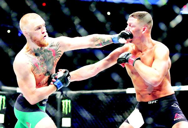 Conor McGregor (left), punches Nate Diaz during their welterweight mixed martial arts bout at UFC 202 on Aug 20, in Las Vegas. McGregor won by split decision. (AP)