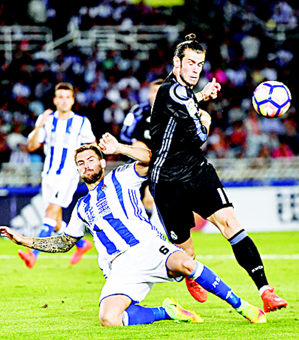 Real Madrid's Gareth Bale (right), in action with Real Sociedad's Inigo Martinez (right), during the Spanish La Liga soccer match between Real Madrid and Real Sociedad, at Anoeta Stadium in San Sebastian, northern Spain on Aug 21. (AP)
