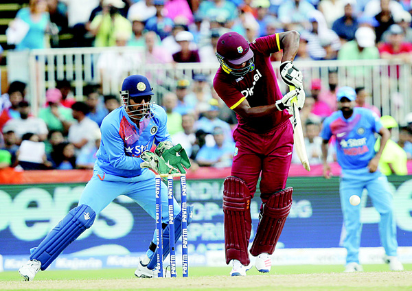 West Indies' Johnson Charles (right), bats as India's wicket keeper MS Dhoni looks on during the first Twenty20 international cricket match on Aug 27, in Lauderhill, Fla. (AP)