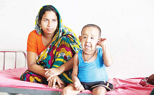 In this photograph taken on Aug 7, four-year-old Bangladeshi child Bayezid Shikdar (right), sits with his mother Tripti Khatun on a bed at Dhaka Medical College Hospital in Dhaka. (AFP