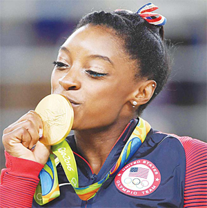 US gymnast Simone Biles celebrates on the podium of the women's fl oor event fi nal of the artistic gymnastics at the Olympic Arena during the Rio 2016 Olympic Games in Rio de Janeiro on Aug 16. (AFP)