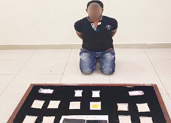 The alleged drug trafficker pictured with his merchandize.