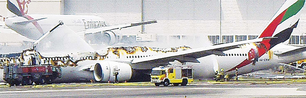 A picture shows a Boeing 777 of the UAE airliner Emirates after it caught fire following a crash landing at Dubai airport on Aug 3. The plane coming from India with 300 people on board crash landed and caught fire in Dubai, causing the death of a firefighter and a four-hour shutdown of the busy airport but no fatalities among passengers. (AFP)
