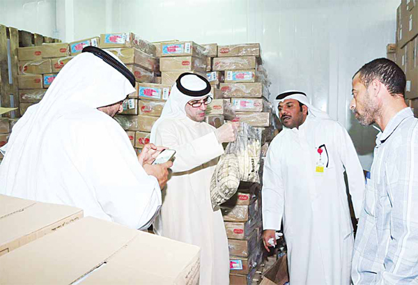 Municipality officials in one of the food stores in Shuwaikh
