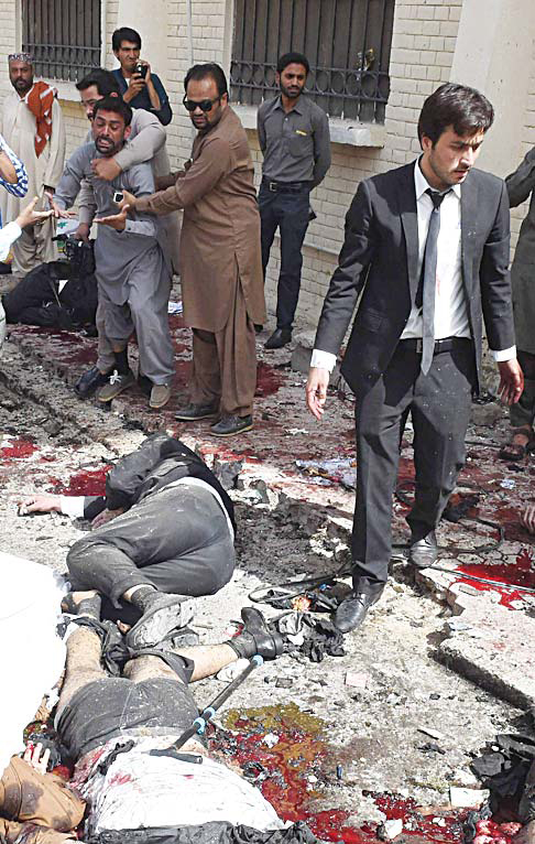 Pakistani lawyers react as they walk near the bodies of their colleagues at the site of a bomb explosion at a government hospital premises in Quetta on Aug 8. At least 70 people were killed after a bomb went off at a major hospital in the southwest Pakistani city of Quetta, an AFP reporter and officials said. (AFP)