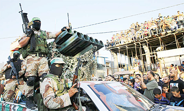 Palestinian masked members from the Izzedine al-Qassam Brigades, a military wing of Hamas, ride vehicle next to a rocket launcher during a rally in Rafah refugee camp, Gaza Strip on Aug 21.