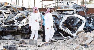 Saudis walk past wreckages at a market for vehicles on Aug 27, in the Saudi border city of Najran, a week after it was struck by a rocket fired from Yemen.