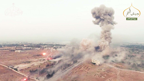 An image grab taken from a video released on Aug 6, by Fateh al-Sham Front, the former Al-Nusra Front, which renamed itself after renouncing its status as al- Qaeda's Syrian affiliate, shows a still from drone footage of smoke billowing from an artillery school south of Aleppo as Islamist rebels captured two military academies and a third military position. (AFP)