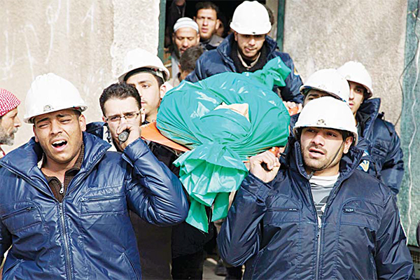 In this Sept 16, 2015 file photo, comrades carry Ilias Mahmoud al-Taweel, a member of Syrian Civil Defense, or White Helmets, during his funeral in Douma, the suburbs of Damascus. Taweel died while rescuing victims of the shelling of the city. (AP)