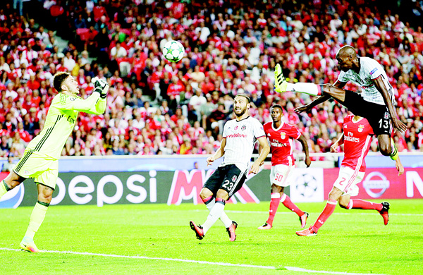 Besiktas' Atiba Hutchinson (right), goes for the ball as Benfica's goalkeeper Ederson (left), tries to stop him during the Champions League Group B soccer match between Benfica and Besiktas at the Luz Stadium in Lisbon, on Sept 13. The match ended 1-1. (AP)