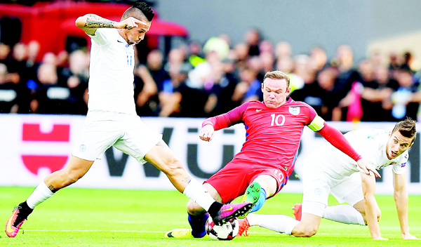 England's forward Wayne Rooney (center), is tackled by Slovakia's midfielder Marek Hamsik (left), and Slovakia's midfielder Jan Gregus during the World Cup 2018 football qualification match between Slovakia and England in Trnava on Sept 4. (AFP)