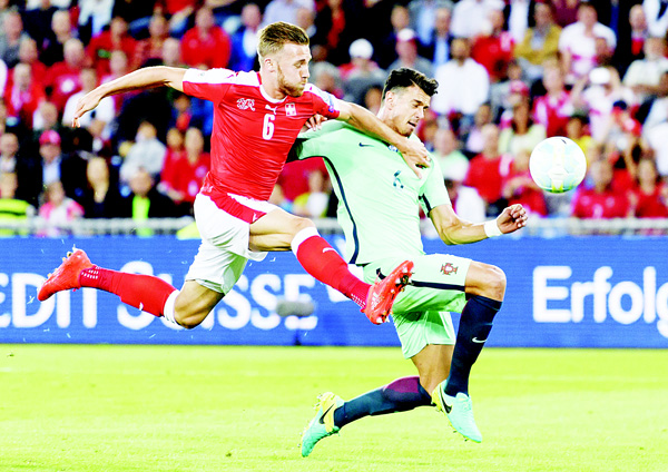 Swiss defender Silvan Widmer (left), vies with Portugal's defender Jose Fonte during the FIFA World Cup WC 2018 football qualifier between Switzerland and Portugal at the St Jakob-Park Stadium in Bael on Sept 6. (AFP)