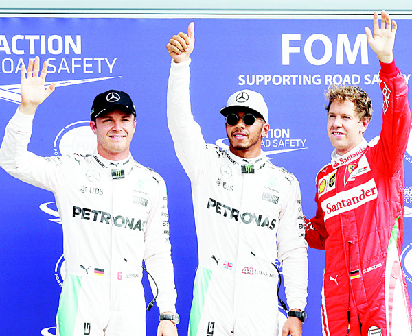 Mercedes driver Lewis Hamilton of Britain (center), celebrates after setting the fastest time with second placed Mercedes driver Nico Rosberg, of Germany (left), and third placed Ferrari driver Sebastian Vettel, of Germany, after the qualifying session for Sunday's Italian Formula One Grand Prix at the Monza racetrack, Italy, on Sept 3. (AP)