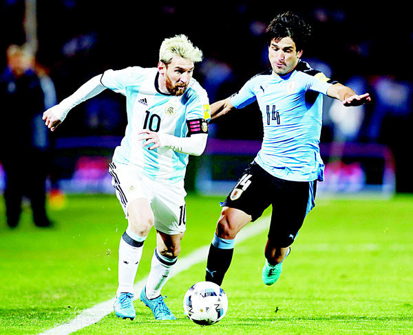 Argentina's Lionel Messi (left), vies for the ball with Uruguay's Nicolas Lodeiro during a 2018 World Cup qualifying soccer match in Mendoza, Argentina, on Sept 1. (AP)
