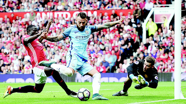 Manchester City's Argentinian defender Nicolas Otamendi (center), attempts to shoot as Manchester United's Ivorian defender Eric Bailly (left), defends and Manchester United's Spanish goalkeeper David de Gea (right), dives during the English Premier League football match between Manchester United and Manchester City at Old Trafford in Manchester, north west England, on Sept 10. (AFP)