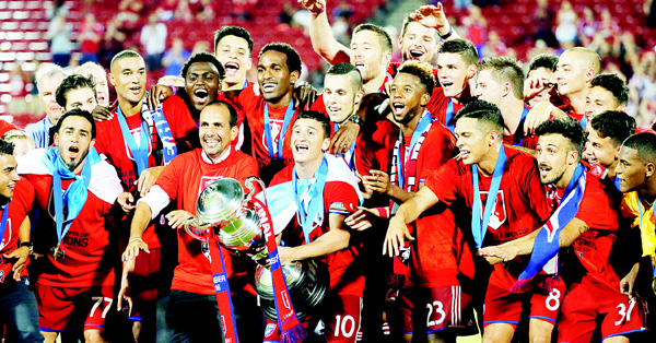 FC Dallas captain Mauro Diaz holds the trophy as he, coach Oscar Pareja (second from left in front), and the rest of the team celebrate a 4-2 win against the New England Revolution in the US Open Cup soccer final on Sept 13, in Frisco, Texas. (AP)